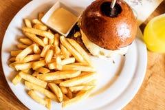 Burger κρέατος και τυριών με τα τηγανητά Στοκ Εικόνα