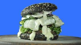 Burger με ένα μαύρο κουλούρι που γεμίζουν με τις φέτες του μαρουλιού αγγουριών και juicy cutlet σε έναν ξύλινο πίνακα και σε ένα  απόθεμα βίντεο