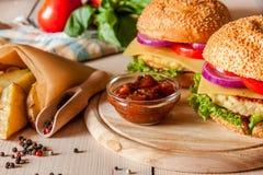 Burger με τα τηγανισμένα potatos Στοκ Φωτογραφία