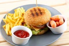 Burger με τη σάλτσα και τα τηγανητά Στοκ Φωτογραφία