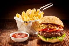 Burger με τις τηγανιτές πατάτες και το κέτσαπ Στοκ φωτογραφία με δικαίωμα ελεύθερης χρήσης