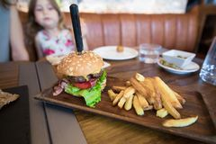 Burger με τις τηγανιτές πατάτες και το μικρό κορίτσι Στοκ εικόνες με δικαίωμα ελεύθερης χρήσης