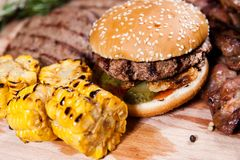 Burger με το καλαμπόκι στον ξύλινο πίνακα Στοκ Εικόνες