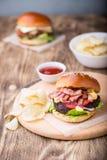 Burger με το μπέϊκον στον ξύλινο πίνακα Στοκ εικόνα με δικαίωμα ελεύθερης χρήσης