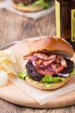 Burger με το μπέϊκον στον ξύλινο πίνακα Στοκ εικόνες με δικαίωμα ελεύθερης χρήσης