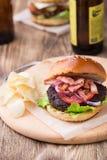 Burger με το μπέϊκον στον ξύλινο πίνακα Στοκ φωτογραφία με δικαίωμα ελεύθερης χρήσης