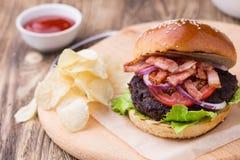 Burger με το μπέϊκον στον ξύλινο πίνακα Στοκ Φωτογραφίες