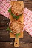 Burger με το μπέϊκον, το arugula και την ντομάτα σε ένα ξύλινο αγροτικό υπόβαθρο Στοκ εικόνες με δικαίωμα ελεύθερης χρήσης