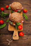 Burger με το μπέϊκον, το arugula και την ντομάτα σε ένα ξύλινο αγροτικό υπόβαθρο Στοκ Φωτογραφία