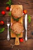 Burger με το μπέϊκον, το arugula και την ντομάτα σε ένα ξύλινο αγροτικό υπόβαθρο Στοκ Φωτογραφίες