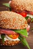 Burger με το μπέϊκον, το arugula και την ντομάτα σε ένα ξύλινο αγροτικό υπόβαθρο Στοκ Εικόνα