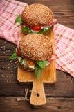 Burger με το μπέϊκον, το arugula και την ντομάτα σε ένα ξύλινο αγροτικό υπόβαθρο Στοκ φωτογραφία με δικαίωμα ελεύθερης χρήσης