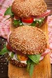 Burger με το μπέϊκον, το arugula και την ντομάτα σε ένα ξύλινο αγροτικό υπόβαθρο Στοκ Εικόνες
