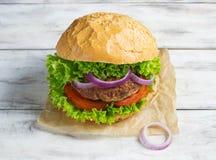 Burger με cutlet, το μαρούλι, τα κρεμμύδια και την ντομάτα βόειου κρέατος Στοκ Εικόνες