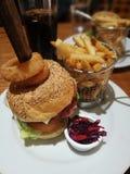 Burger μπέϊκον τυριών με τα τσιπ και το επιλεγμένο κόκκινο λάχανο στοκ εικόνα