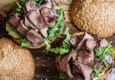 Burger μπριζόλας βόειου κρέατος με τα τουρσιά, mayo τη σάλτσα, το arugula και το κόκκινο κρεμμύδι σε έναν αγροτικό ξύλινο πίνακα, Στοκ Εικόνα