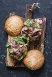 Burger μπριζόλας βόειου κρέατος με τα τουρσιά, mayo τη σάλτσα, το arugula και το κόκκινο κρεμμύδι σε έναν αγροτικό ξύλινο τέμνοντ Στοκ Φωτογραφία