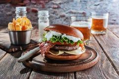 Burger πιάνων με το μπέϊκον και cutlet με το τυρί, ντομάτα, πράσινα στοκ φωτογραφία με δικαίωμα ελεύθερης χρήσης