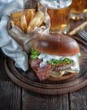 Burger πιάνων με το μπέϊκον και cutlet με το τυρί, ντομάτα, πράσινα στοκ φωτογραφίες με δικαίωμα ελεύθερης χρήσης