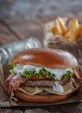 Burger πιάνων με το μπέϊκον και cutlet με το τυρί, ντομάτα, πράσινα στοκ εικόνα με δικαίωμα ελεύθερης χρήσης