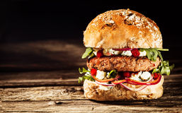 Burger που συσσωρεύεται υψηλό με τα καλύμματα σε ολόκληρο το κουλούρι σιταριού Στοκ Φωτογραφίες