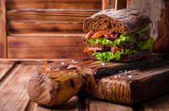 Burger σάντουιτς με το μαρούλι, ψημένο μπέϊκον στο σκοτεινό ξύλινο τέμνοντα πίνακα Εκλεκτική εστίαση Στοκ φωτογραφία με δικαίωμα ελεύθερης χρήσης