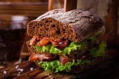 Burger σάντουιτς με το μαρούλι, ψημένο μπέϊκον στο σκοτεινό ξύλινο τέμνοντα πίνακα Εκλεκτική εστίαση Στοκ Εικόνες