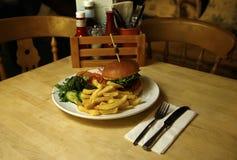 Burger σε ένα brioche κουλούρι με τα τσιπ & τη δευτερεύουσα σαλάτα Στοκ φωτογραφία με δικαίωμα ελεύθερης χρήσης