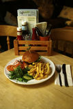 Burger σε ένα brioche κουλούρι με τα τσιπ & τη δευτερεύουσα σαλάτα Στοκ Εικόνες