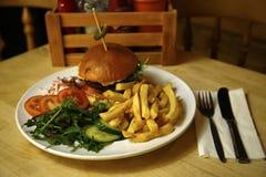 Burger σε ένα brioche κουλούρι με τα τσιπ & τη δευτερεύουσα σαλάτα Στοκ εικόνα με δικαίωμα ελεύθερης χρήσης