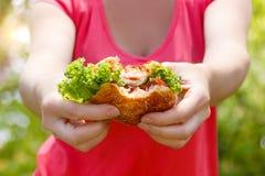 Burger στα χέρια των γυναικών Στοκ φωτογραφία με δικαίωμα ελεύθερης χρήσης