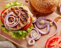 Burger στον ξύλινο πίνακα με το κρεμμύδι και τις ντομάτες στοκ φωτογραφία με δικαίωμα ελεύθερης χρήσης