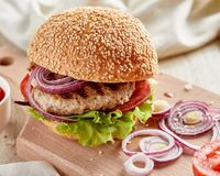 Burger στον ξύλινο πίνακα με το κρεμμύδι και τις ντομάτες στοκ φωτογραφίες