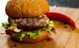Burger στον ξύλινο πίνακα Στο σκοτεινό υπόβαθρο Στοκ φωτογραφίες με δικαίωμα ελεύθερης χρήσης