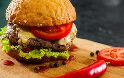 Burger στον ξύλινο πίνακα Στο σκοτεινό υπόβαθρο Στοκ φωτογραφία με δικαίωμα ελεύθερης χρήσης
