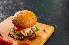 Burger στον ξύλινο πίνακα Στο σκοτεινό υπόβαθρο Στοκ εικόνες με δικαίωμα ελεύθερης χρήσης