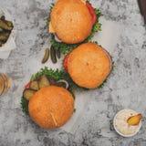 Burger τρία με τα τηγανητά σε μια άσπρη επιφάνεια Στοκ εικόνες με δικαίωμα ελεύθερης χρήσης