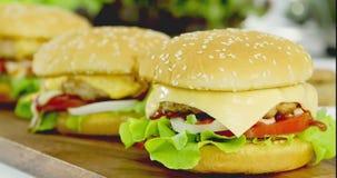 Burger τυριών με την ντομάτα, το κρεμμύδι και το μαρούλι απόθεμα βίντεο