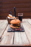 Burger τυριών μπέϊκον, περικοπές πατατών και κοκ στον πίνακα Στοκ Εικόνες
