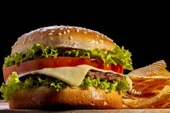 Burger. With chips focus on front in black background stock photos