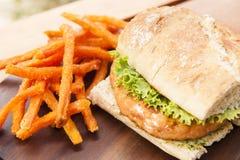 Burger σολομών με τα τηγανητά γλυκών πατατών Στοκ Εικόνα