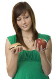 Burger or apple. Female teenager choose food Stock Photos