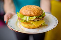 Burger auf einer Platte in der Hand stockbilder