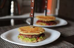 Burger with beef chops, guacamole, cherry sauce, potato bun on the grill. Stabbed with a knife with a wooden handle Royalty Free Stock Photos