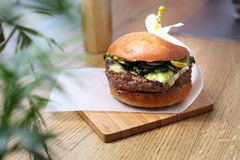 Burger with beef cutlet with green salad and grilled green vegetables stock images