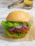 Burger with beef cutlet, lettuce, onions and tomato Royalty Free Stock Photography
