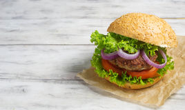 Burger with beef cutlet, lettuce, onions and tomato Royalty Free Stock Images
