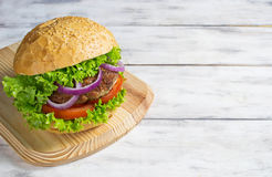 Burger with beef cutlet, lettuce, onions and tomato Stock Image