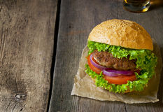 Burger with beef cutlet, lettuce, onions and tomato Stock Photos