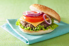 Burger with beef patty cheese lettuce onion tomato Stock Photography